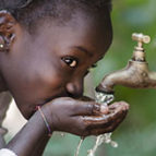 a young black girl drinks clean water from a faucet